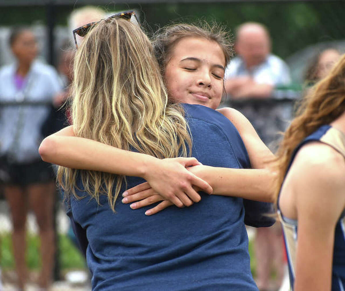Father McGivney freshman Kaitlyn Hatley hugs a coach after her win in the 800-meter run at the Class 1A Belleville Althoff Sectional.