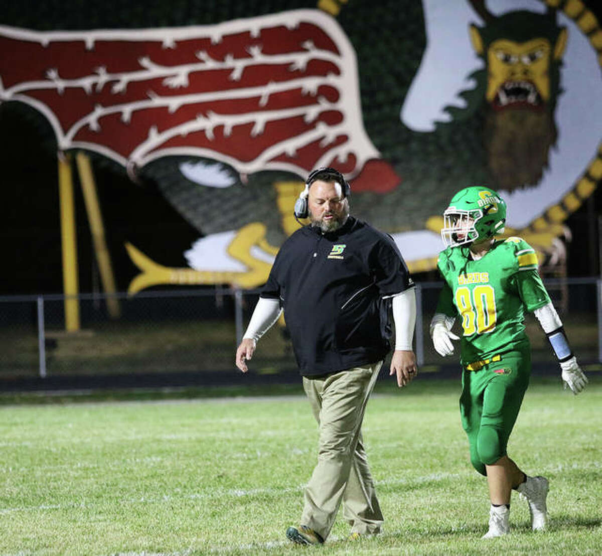 Southwestern coach Pat Keith (left) walks onto the field with one of his players during a game in 2019 at Knapp Field in Piasa.
