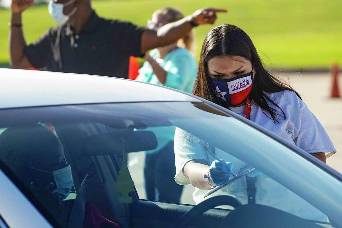 An election worker accepts mail in ballot from a voter at drive-through mail ballot drop off site at NRG Stadium on October 7, 2020 in Houston, Texas.