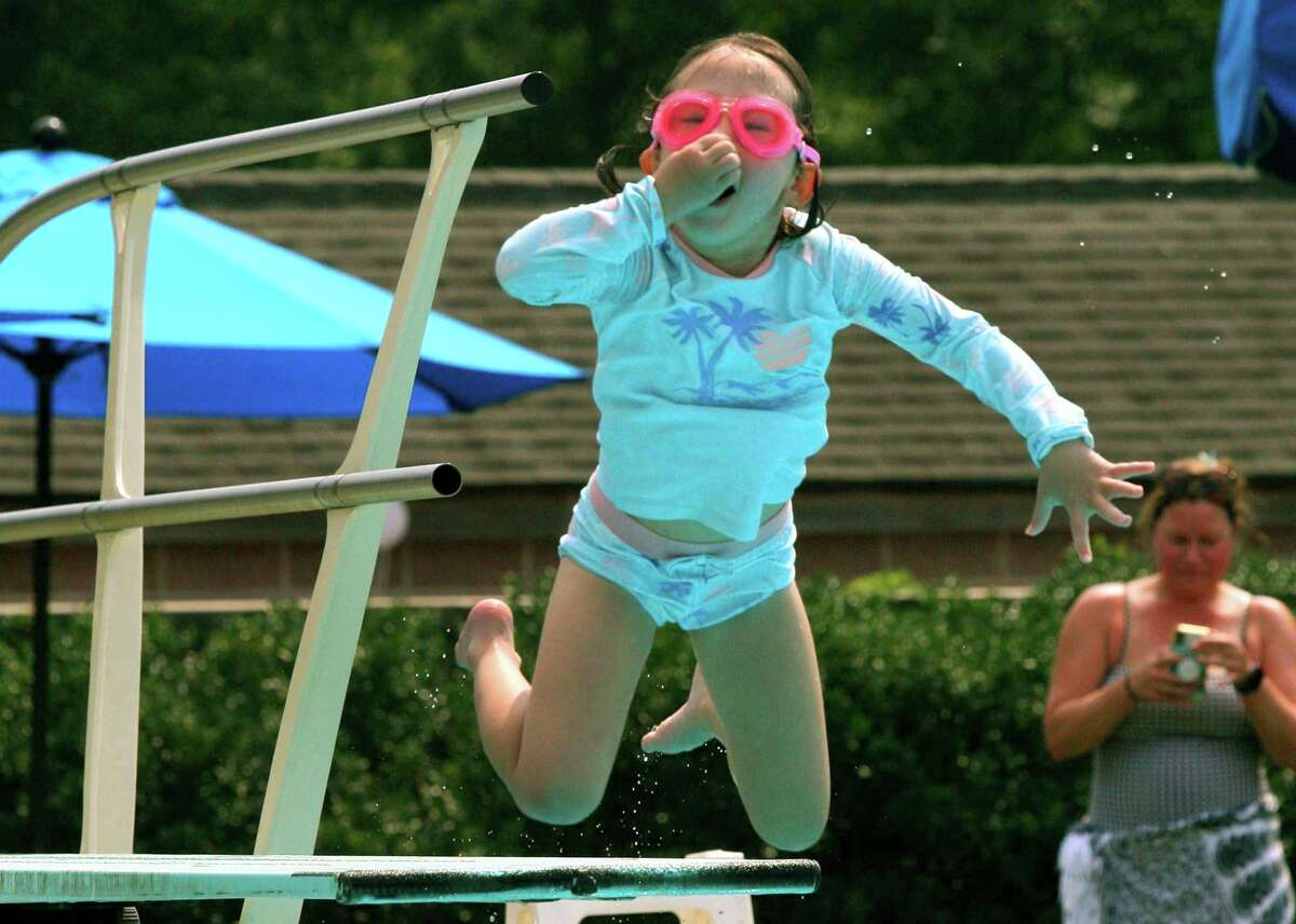 Charlie Harbold, 6, holds her nose as she jumps off of the diving board at Waveny Park's swimming pool in New Canaan, Conn., on Tuesday July 27, 2021.