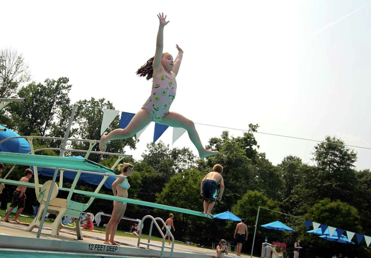 Emmy Taylor, 7, leaps off of the diving board while spending time beating the heat at Waveny Park's swimming pool in New Canaan on Tuesday.