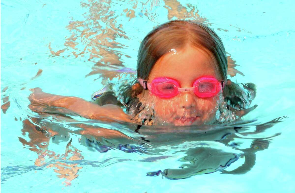 Carolina Mannle, 8, swims around in the shallow end at Waveny Park's swimming pool in New Canaan, Conn., on Tuesday July 27, 2021.