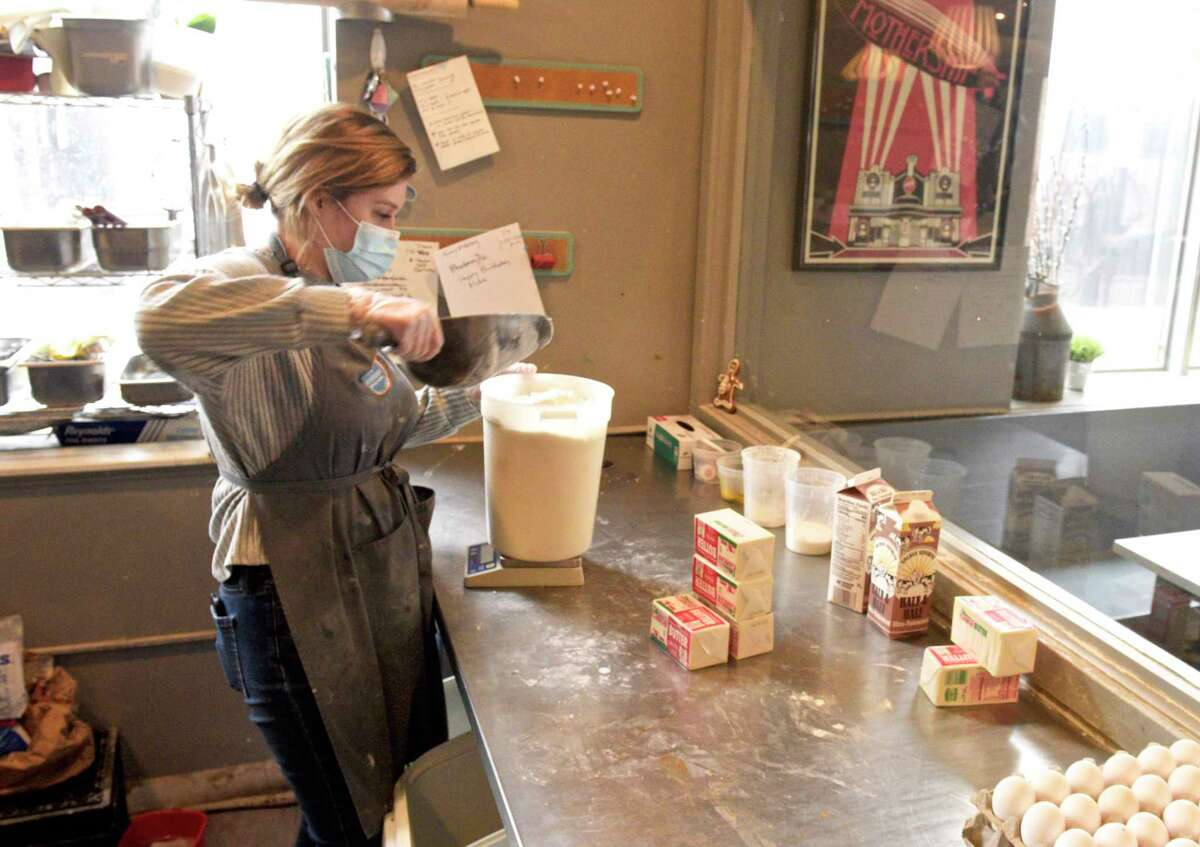A Mothership on Main baker measures out ingredients for brioche in January 2021, in Danbury, Conn. Mothership is among the Connecticut eateries hiring in the summer of 2021, months after owner Anna Llanos opened a second Danbury fusion restaurant called ItadakiMÁS.