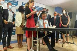 Lt. Gov. Susan Bysiewicz and Gov. Ned Lamont lead a ceremonial bill signing in Hartford on Tuesday for two recently adopted bills designed to strengthen Connecticut's gun safety regulations.