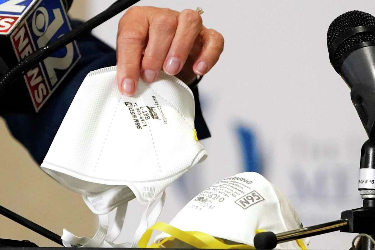 Dr. LouAnn Woodward, vice chancellor for health affairs and dean of the School of Medicine at the University of Mississippi Medical School, displays N95 face masks on Friday, July 16, 2021, during a news conference in Jackson, Miss.