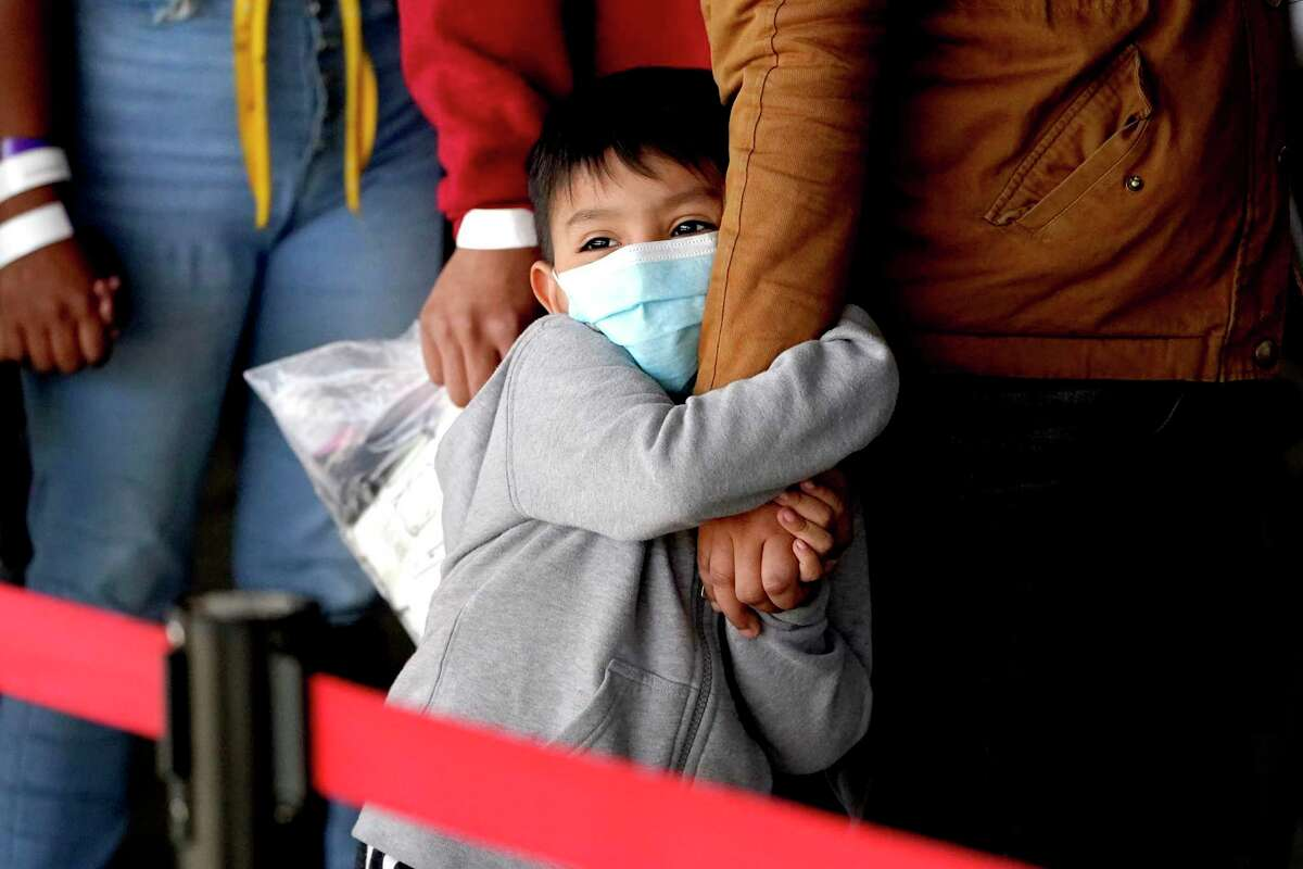 A migrant child holds onto a woman's arm as they wait to be processed by a humanitarian group after being released from U.S. Customs and Border Protection custody at a bus station, Wednesday, March 17, 2021, in Brownsville, Texas.