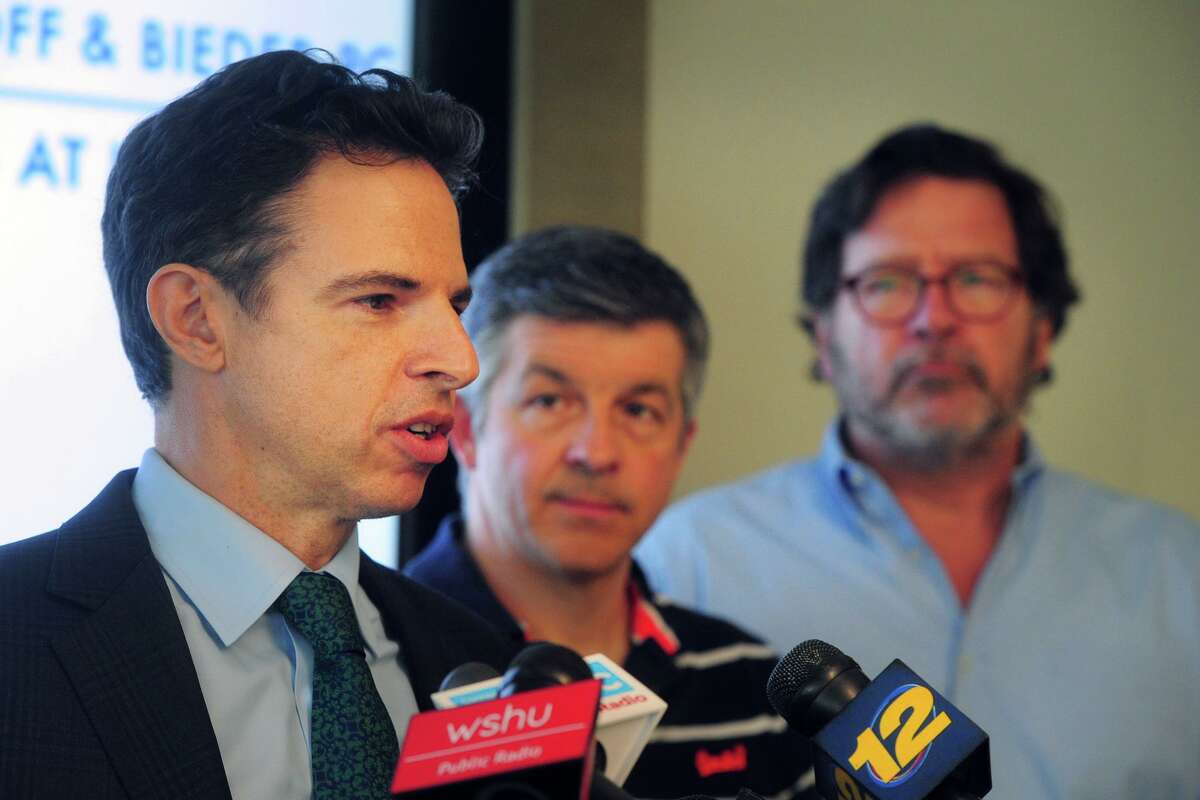 Attorney Josh Koskoff speaks at a 2019 news conference in Bridgeport. Court documents filed Tuesday show Remington Arms Co. offering millions to settle lawsuits filed by nine families affected by the Sandy Hook Elementary School shooting. With Koskoff was Ian Hockley, center, father of Sandy Hook student Dylan Hockley, and Bill Sherlach, right, husband of Sandy Hook psychologist Mary Sherlach, Dylan Hockley and Mary Sherlach were killed in the attack.