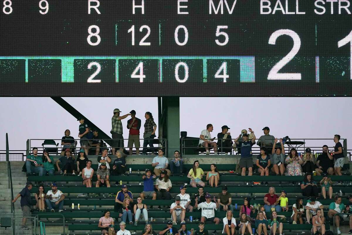 Fans sit in the outfield bleachers under a video display during a baseball game between the Seattle Mariners and the Houston Astros, Tuesday, July 27, 2021, in Seattle. (AP Photo/Ted S. Warren)