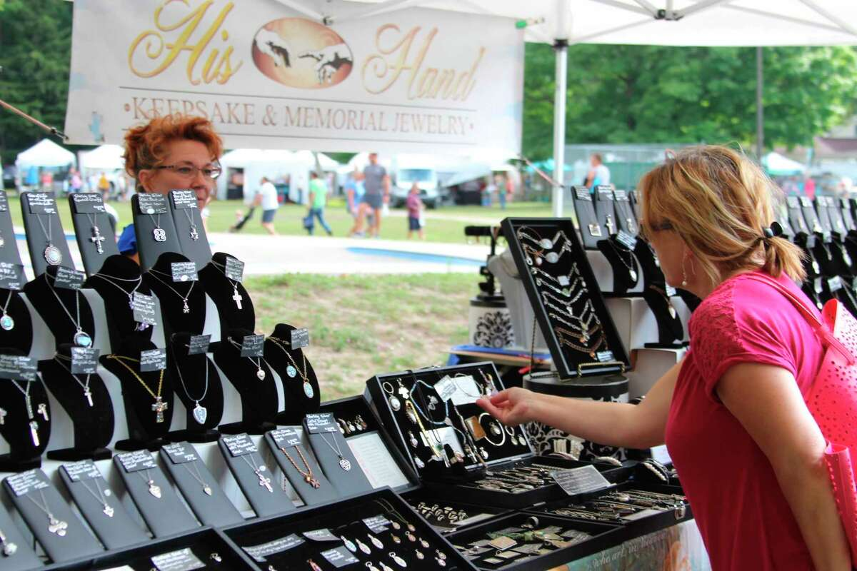 A visitor at the 2019 Frankfort Art Fair looks at jewelry. (Courtesy photo)