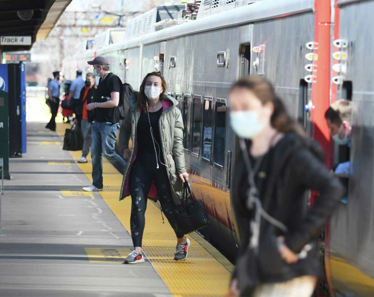 Passengers disembark from a northbound Metro-North train at the central Greenwich train station in Greenwich, Conn. Wednesday, April 7, 2021.