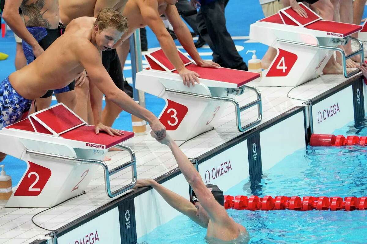 Kieran Smith helps Townley Haas out of the pool after the United States finished fourth in the 4x200 relay.