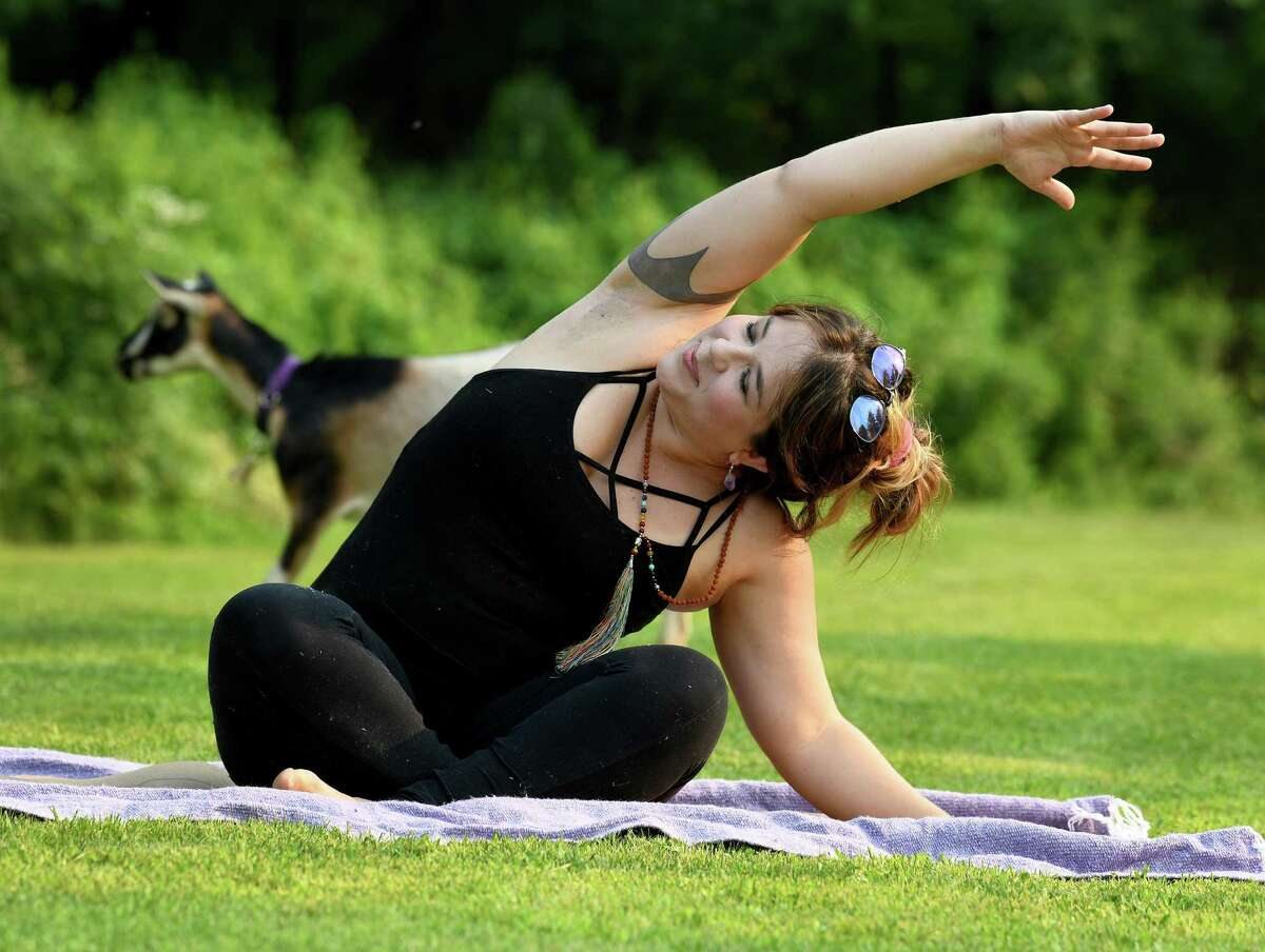 Danbury resident Kathleen Kweskin, CEO and founder of Grow Wellness in Ridgefield, leads a session of goat yoga on Monday, July 26, 2021 in Ridgefield, Conn.