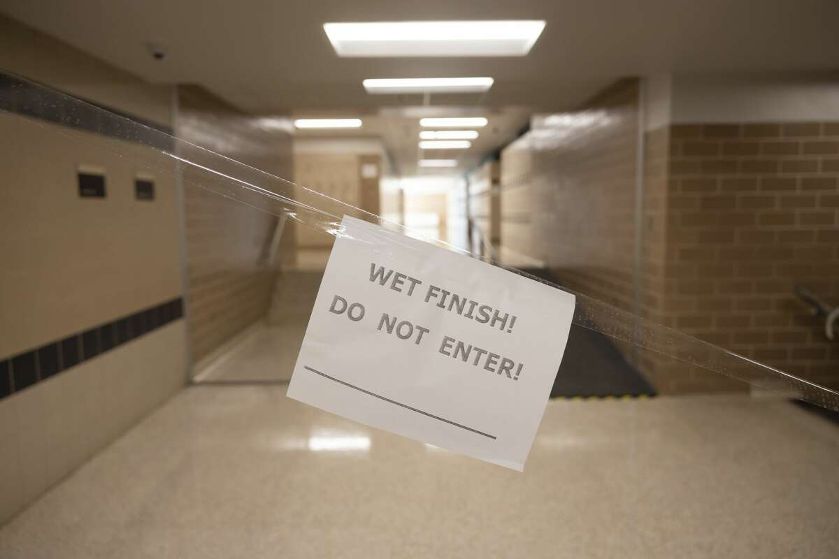 A paper sign is forbidding entry due to wet finish is seen in the hallways of Conroe High School, Thursday, July 22, 2021, in Conroe.