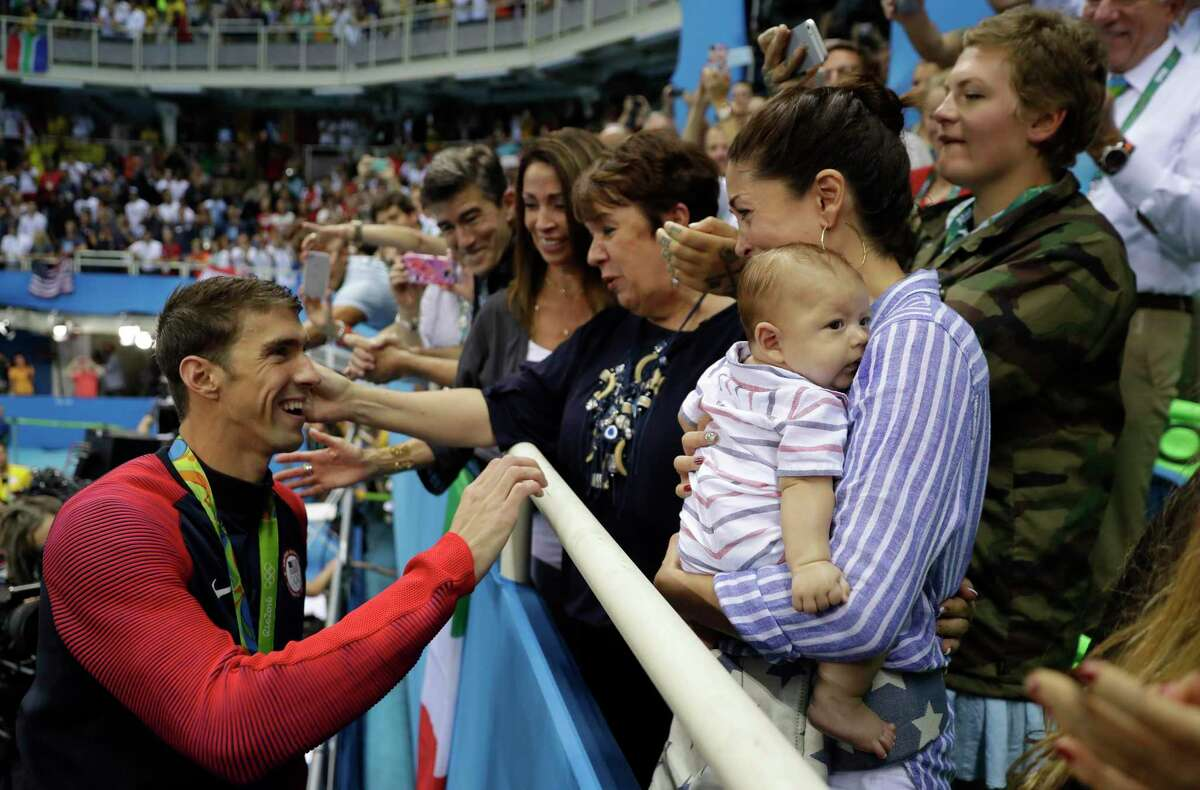 FILE - In this Tuesday, Aug. 9, 2016, file photo, United States' Michael Phelps celebrates winning his gold medal in the men's 200-meter butterfly with his mother Debbie, fiance Nicole Johnson and baby Boomer during the swimming competitions at the 2016 Summer Olympics in Rio de Janeiro, Brazil. Private, touching moment between loved ones won't be happening at the pandemic-delayed Tokyo Olympics. No spectators - local or foreign - will be allowed at the majority of venues, where athletes will hang medals around their own necks to protect against spreading the coronavirus. No handshakes or hugs on the podium, either. (AP Photo/Matt Slocum, File)