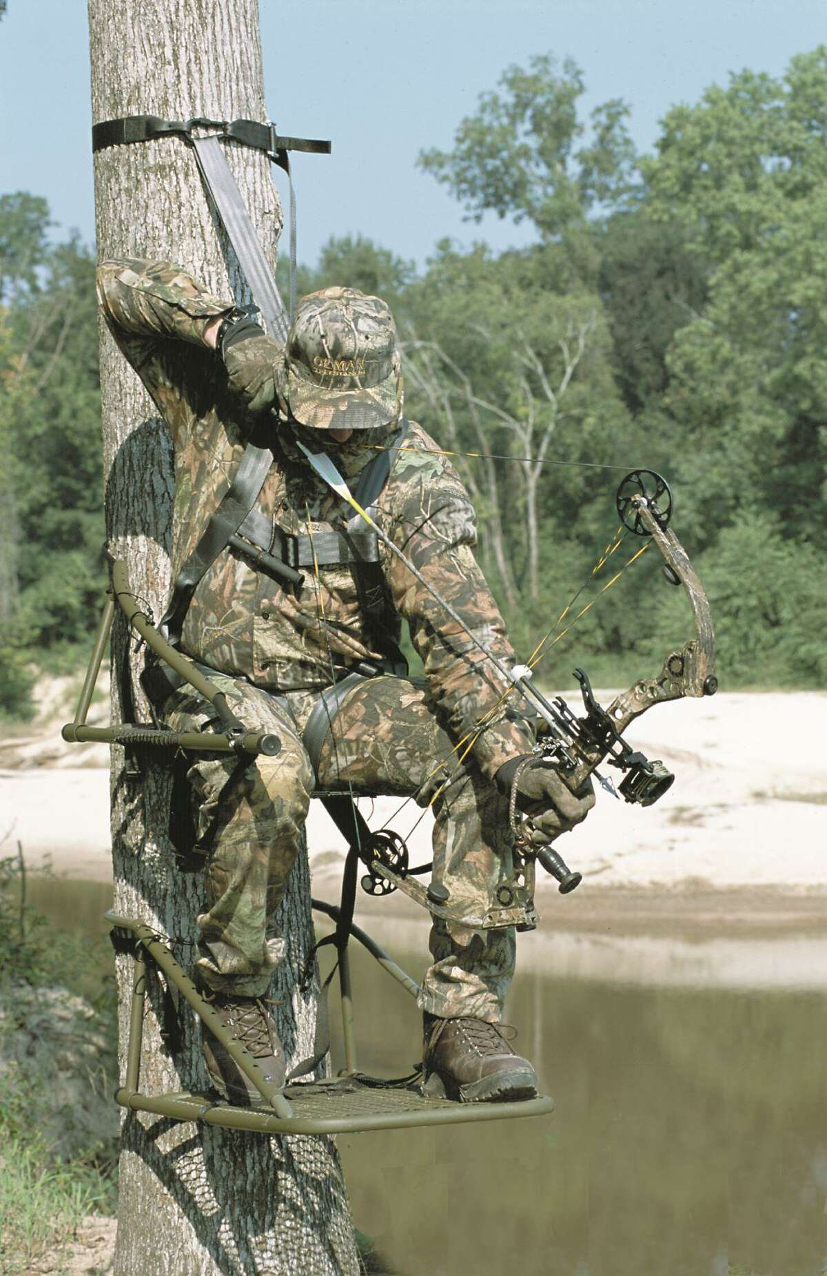 This bow hunter is in a tree stand and with the proper camouflage and all of the safety equipment.