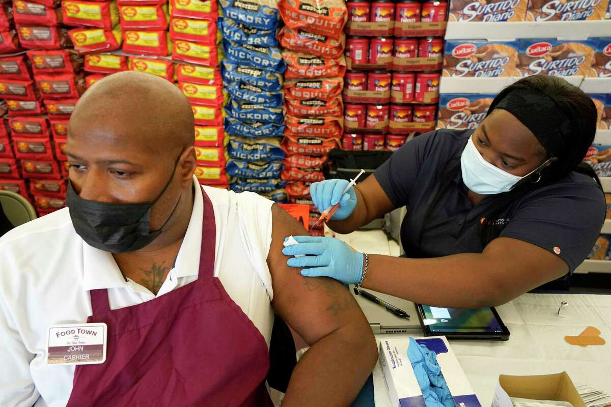 John Jones, cashier, left, receiveS a Pfizer vaccination from Kiosha Martin, LVN, right, with Houston Health Department, during an event held at Food Town, 5367 Antoine Dr., Tuesday, July 27, 2021 in Houston.