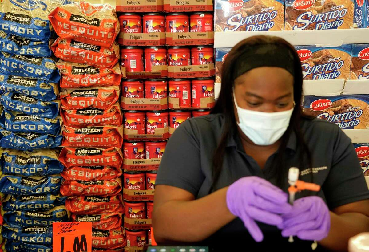 Kiosha Martin, LVN, with Houston Health Department, is surrounded by grocery items as she prepares a Pfizer vaccination during an event held at Food Town, 5367 Antoine Dr., Tuesday, July 27, 2021 in Houston.