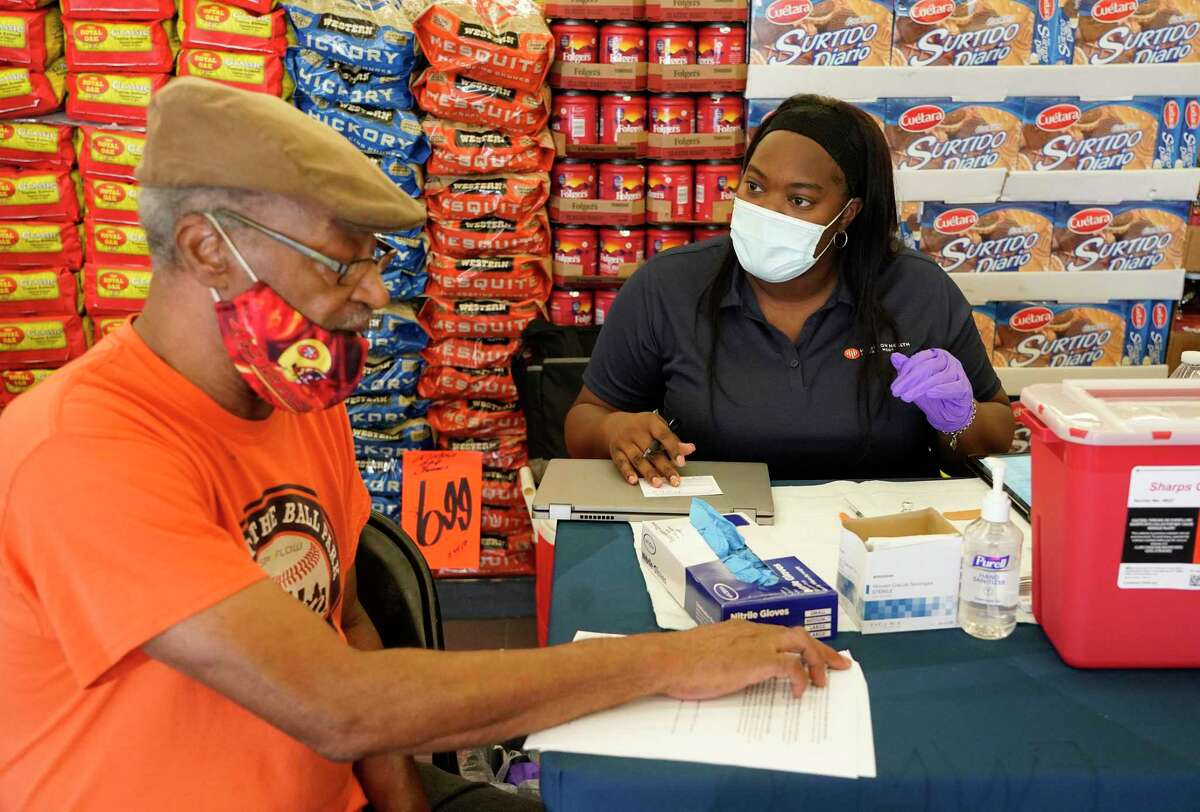 David Brown, left, talks to Kiosha Martin, LVN, right, with Houston Health Department, about getting a vaccination during an event held at Food Town, 5367 Antoine Dr., Tuesday, July 27, 2021 in Houston. After seeing the possible side effects, he decided not to take the vaccination.