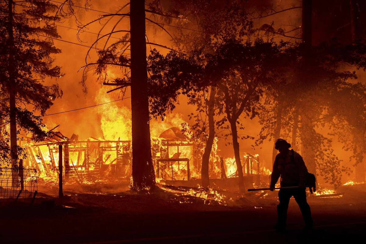 In this Saturday, July 24, 2021, file photo a firefighter passes a burning home as the Dixie Fire flares in Plumas County, Calif. The fire destroyed multiple residences as it tore through the Indian Falls community.