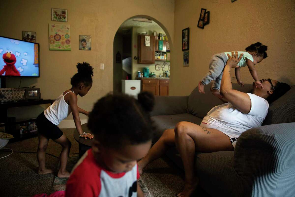 Brittany Baker plays with her children, Aubriana, 4, Jordan, 2, and Kaitlyn, 1, in their Dayton home.