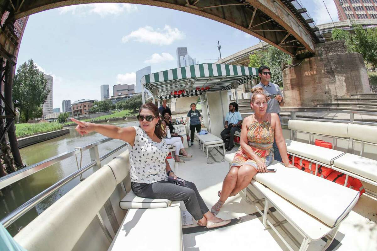 Amy Vargas (left) points toward a mural with her co-workers Rebecca Leija and Juan Sorto during a Buffalo Bayou Partnership boat tour Tuesday, July 20, 2021, in Houston. The Buffalo Bayou Partnership recently reopened boat tours to the public.