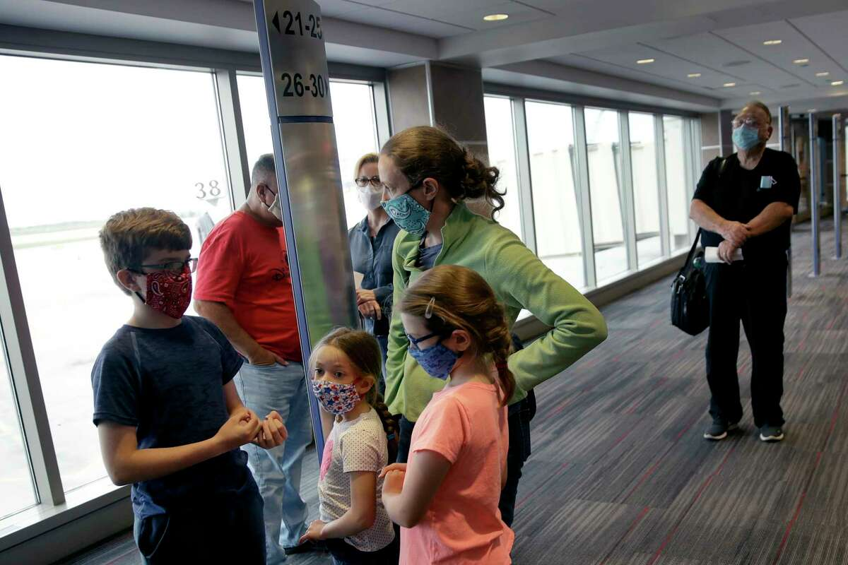 FILE - People wearing masks wait to board a Southwest Airlines flight at Kansas City International airport in Kansas City, Mo., in this May 24, 2020, file photo. Governments and businesses are scrambling to change course following new federal guidance calling for the return of mask wearing in virus hot spots amid a dramatic spike in COVID-19 cases and hospitalizations nationwide. Nevada and Kansas City were among the locations that moved swiftly to re-impose indoor mask mandates following Tuesday's, July 27, 2021, announcement from the Centers for Disease Control and Prevention.