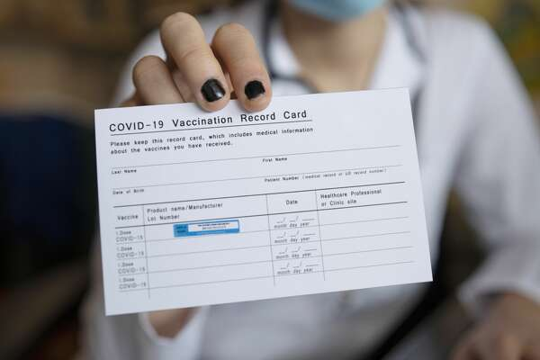 Close up of person holding a COVID-19 vaccination record card.