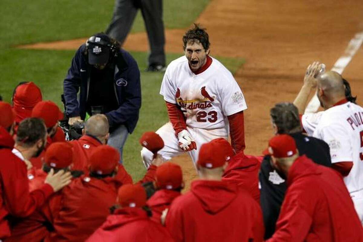 David Freese of the Cardinals is met by teammates after his game-winning home run in Game 6 of the 2011 World Series against the Texas Rangers.