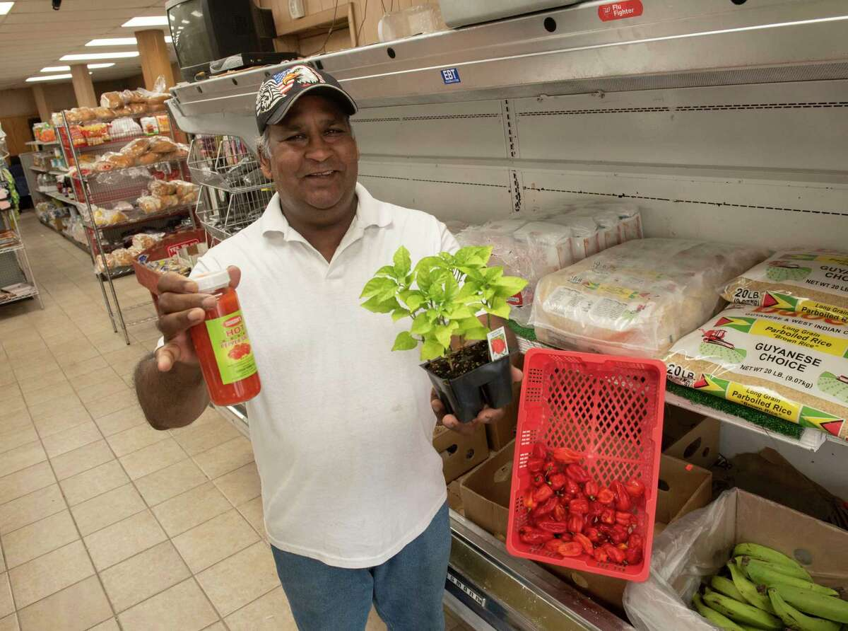 Ramesh Doodnauth holds up a hot pepper plant and a jar of hot pepper sauce in his Ramesh West Indian Grocery Store on Tuesday, July 27, 2021 in Schenectady, N.Y. (Lori Van Buren/Times Union)