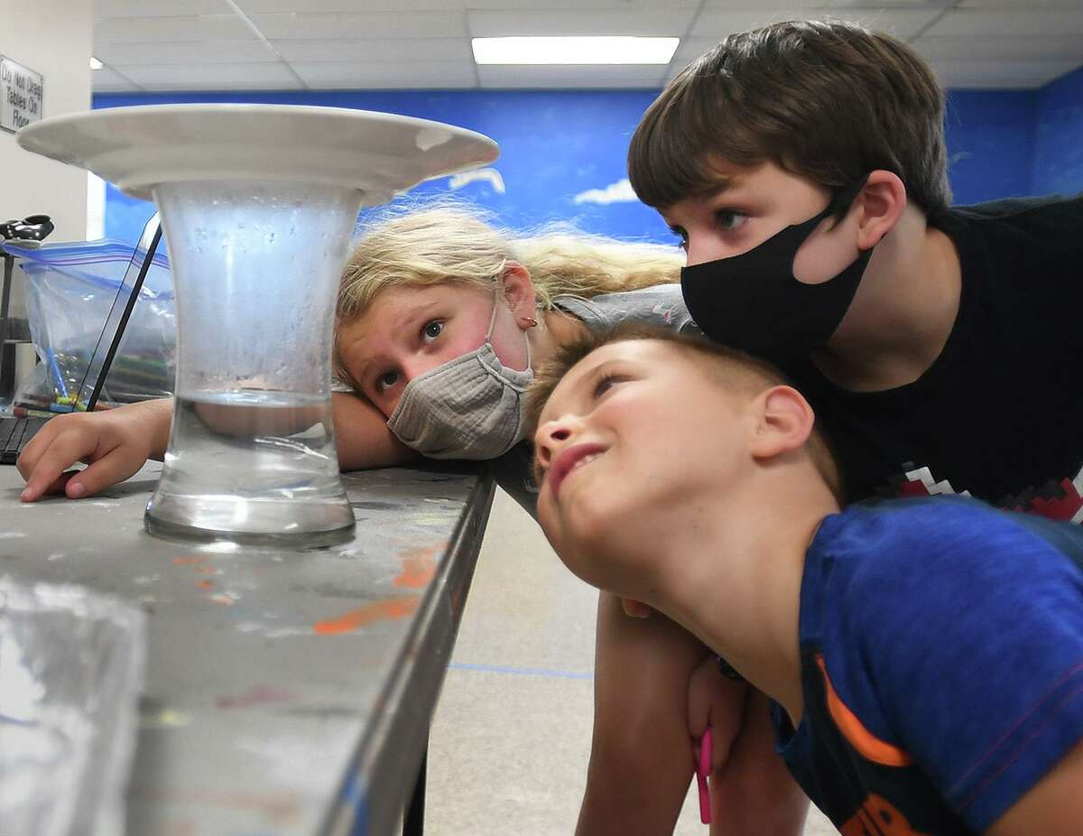 From left; Remi Brenner, 9, Michael Pietrini, 6, and Ian Bear, 9, check out the rain cloud they created during the Milford Recreation Department's one week summer meteorology camp at the Tri Beach Center in Milford, Conn. on Tuesday, July 27, 2021.