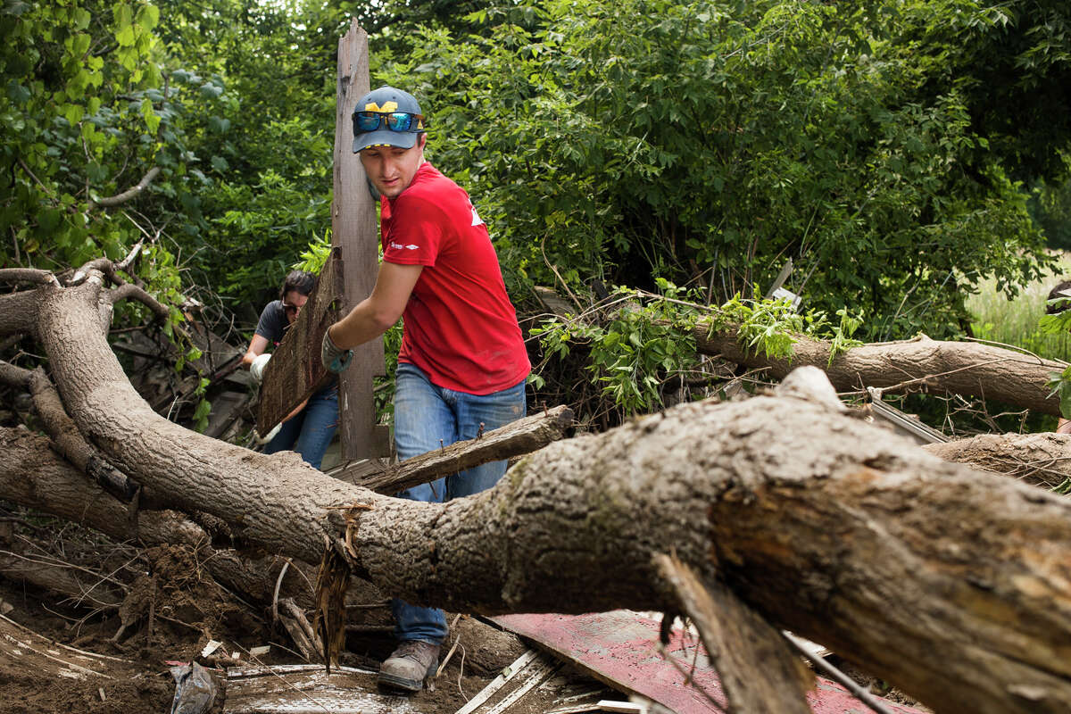 Stephanie Barbon, left, and Sean Bremer, center, carry a piece of wood as about 100 volunteers work to clear flood debris from downtown Sanford during an event hosted by United Way of Midland County and other local organizations Wednesday, July 28, 2021. (Katy Kildee/kkildee@mdn.net)