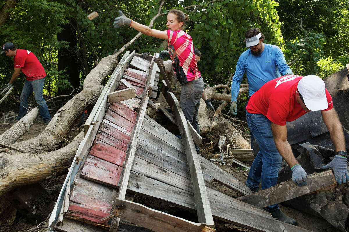 Bridget Connor, center, tosses a piece of wood onto a pile as about 100 volunteers work to clear flood debris from downtown Sanford during an event hosted by United Way of Midland County and other local organizations Wednesday, July 28, 2021. (Katy Kildee/kkildee@mdn.net)