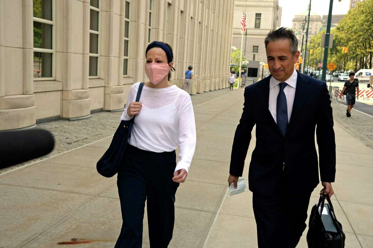 Lauren Salzman, left, walks to Federal District Court in Brooklyn for sentencing on Wednesday, July 28, 2021. Prosecutors sought a reduced sentence for Lauren Salzman, who detailed the inner workings of the cultlike NXIVM group in four days of testimony that helped to convict Keith Raniere.