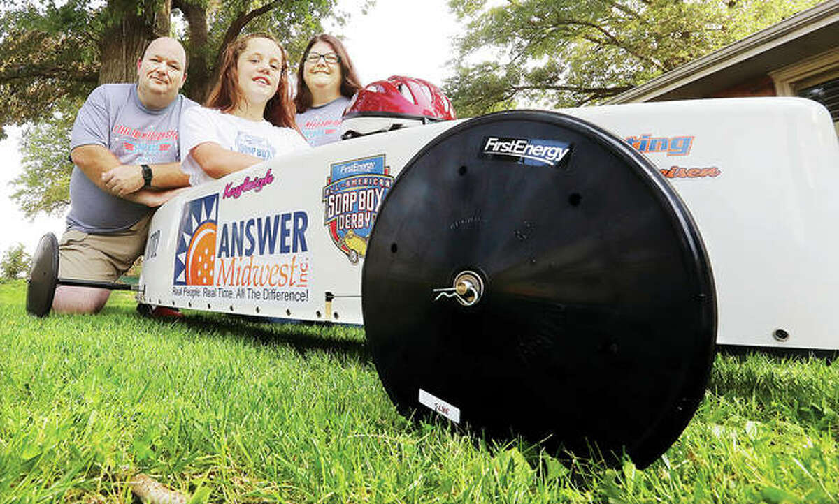 Kayleigh Pollock, 11, sits in her winning soapbox derby racer with her dad, Don, and mother, Chrissy, in front of their Godfrey home. Pollock, who qualified in regional races, placed 9th in the All-American Soapbox Derby World Championships in Akron, Ohio, last weekend.