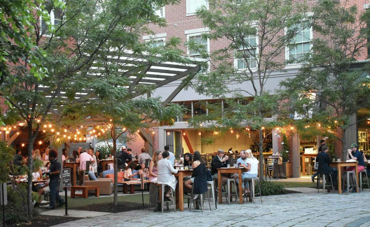 Patrons throng an outdoor seating area with greenery on June 30, 2020, at The Spread's new location on a cul-de-sac just off Washington Street in South Norwalk, Conn.