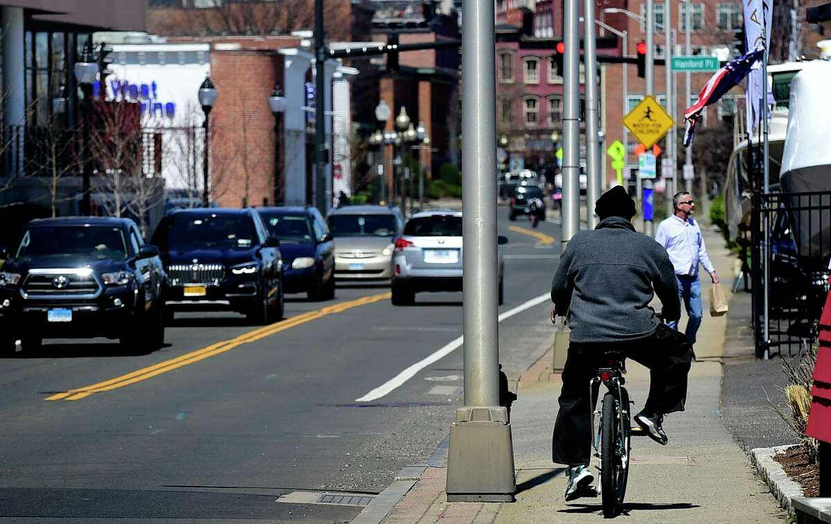 A bicyclists rides on the sidewalk along Route 136 at Water Street Tuesday, April 6, 2021, in Norwalk, Conn.