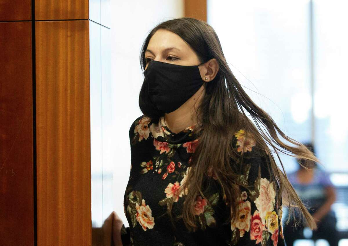 Christine Fesus, 34, walks into District Judge Chris Morton's courtroom on July 28, 2021, to address bail conditions over her murder charge in the death of DeAndrea Citizen outside a north Harris County grocery store.