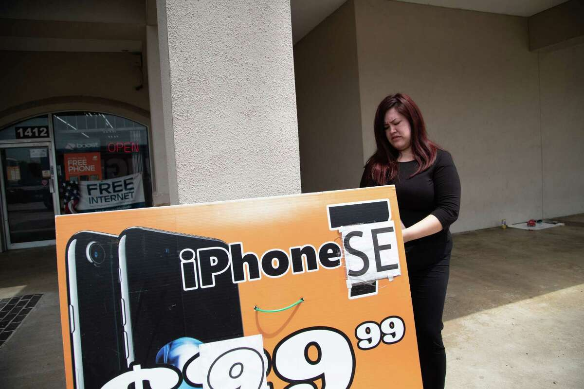 Ilsee Diaz, an employee at Boost Mobile in the 1400 block of FM 1960, attaches a sign on July 27, 2021, near a small memorial for DeAndrea Citizen.