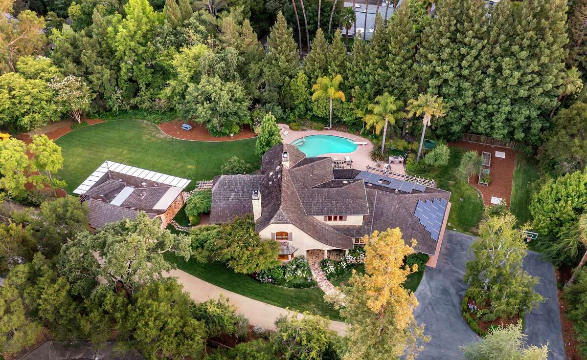 The grounds include a main house, a guest home, a swimming pool with a diving board, an outdoor kitchen and a fire pit.
