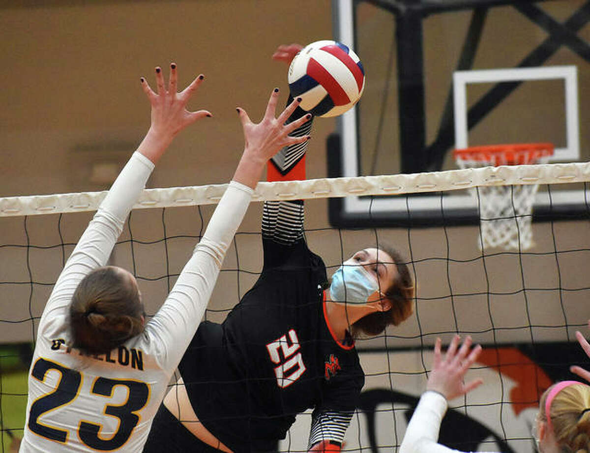 Edwardsville senior Storm Suhre (20) hits over the block of O'Fallon's Valarie Finck (23) during a season-opening match March 16 in Edwardsville. Suhre, a 6-2 middle blocker signed with Indiana State, is the 2020 Telegraph Large-Schools Girls Volleyball Player of the Year.