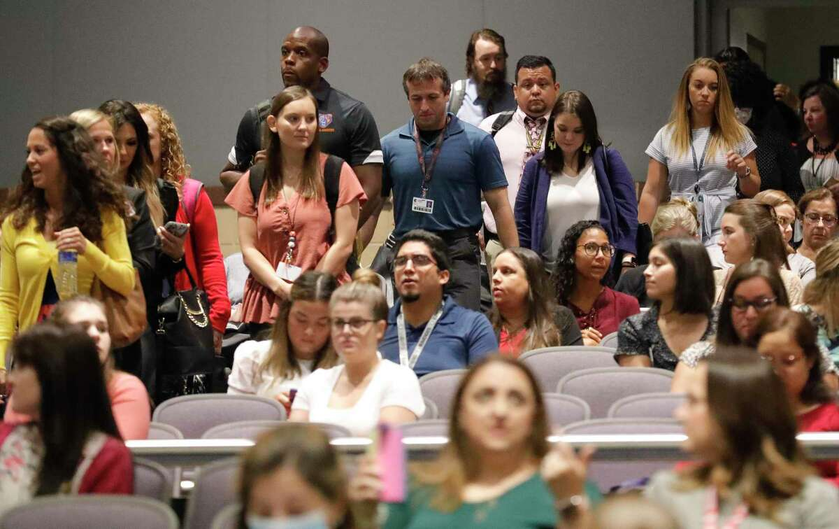 New teachers file into the auditorium at Grand Oak High School for the first day of new teacher orientation, Wednesday, July 28, 2021, in Spring. The district hired more than 600 teachers for the upcoming school year.