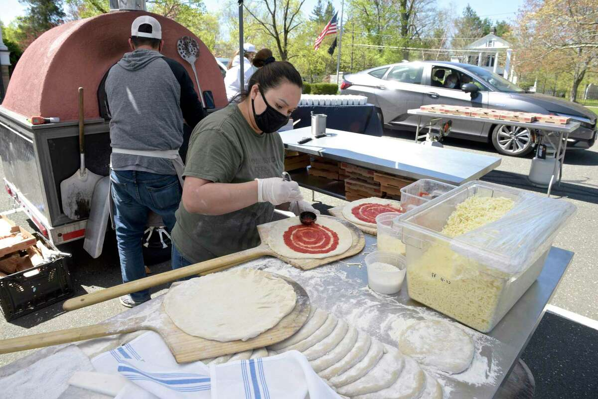 Alorfa Escoboda, from Bailey's Backyard Pizza Pop-Up, makes pizza's for a drive-thru senior lunch at Lounsbury House in Ridgefield, Conn, on Monday, April 26, 2021. Mask-wearing continues to be optional at Lounsbury House.