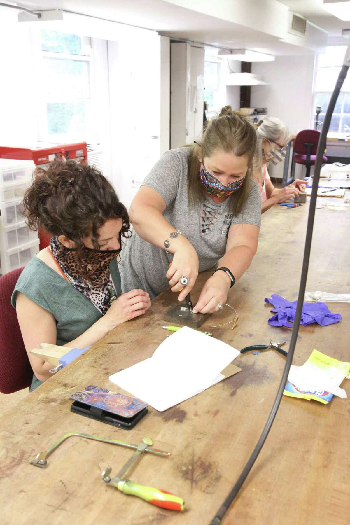 Instructor Maureen Henriques, of New Milford, discusses the making of a bezel with Laurieann Steckler of Holmes, N.Y., during a recent Brookfield Craft Center class on sandcasting. At the Brookfield Craft Center, masks are required for all instructors and students participating in programs at the center's studios.