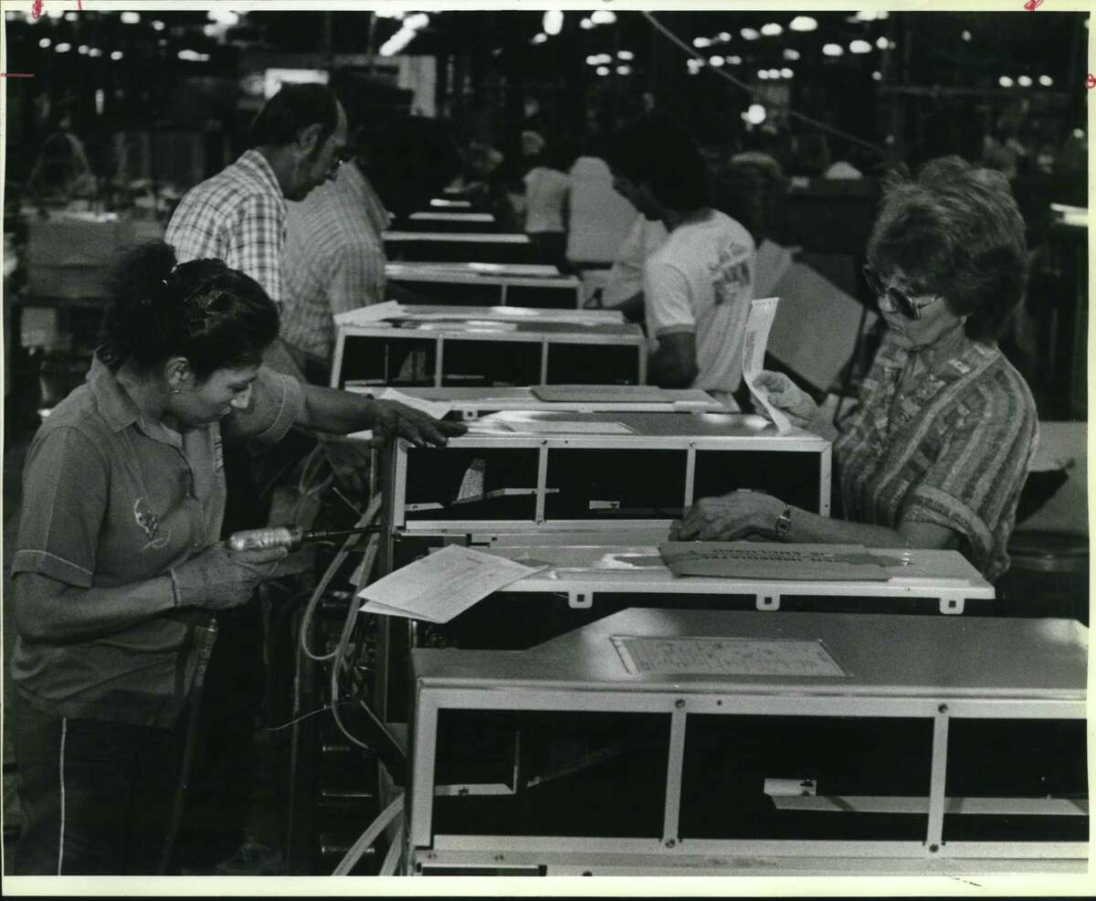 Assembly workers Juanita Rojas and Mary Jonas put finishing touches on air conditioningunits at Friedrich Air Conditioningin 1985.