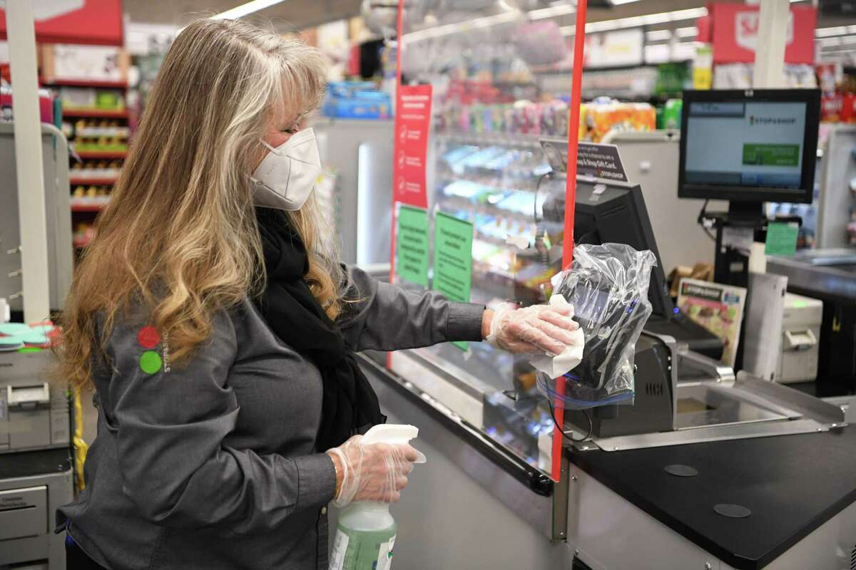 A Stop & Shop employee sanitizes a checkout line in April 2020 at a store in Connecticut.