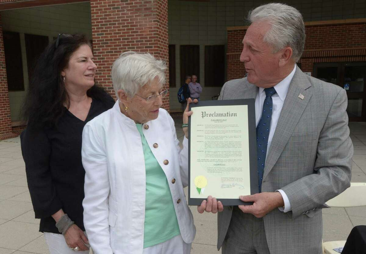 """The Norwalk / Nagarote Sister City Project project manager Catherine Bagg and director Tish Gibbs accept the """"Proclamation of Nagarote Day"""" from Norwalk Mayor Harry Rilling as the organization celebrates Norwalk's Sister City, Nagarote, Nicaragua, Friday, June 16, 2017, by handing out wrist bands and literature in front of Norwalk City Hall in Norwalk, Conn."""