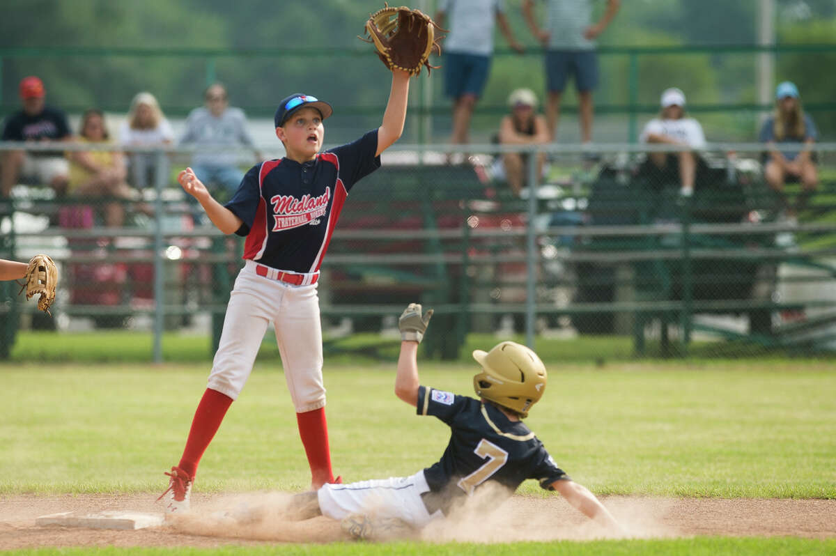 Midland Fraternal Northwest's Eli Piotrowski jumps up in an attempt to catch the ball and tag a runner during a state semifinal game against Grosse Pointe Farms-City Wednesday, July 28, 2021 in Bay City. (Katy Kildee/kkildee@mdn.net)