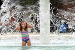 Amelia Cook gets doused in the fountain while cooling off at the Alice Keith Park pool Tuesday, which was the first day of the hottest weeks of summer, according to Space City Weather. Photo made Tuesday, July 27, 2021 Kim Brent/The Enterprise