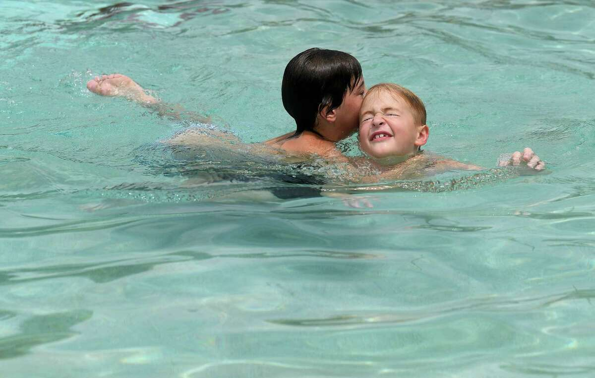 Hayden Robins (left) and neighbor friend Jackson Cook horse around while cooling off at the Alice Keith Park pool Tuesday, which was the first day of the hottest weeks of summer, according to Space City Weather. Photo made Tuesday, July 27, 2021 Kim Brent/The Enterprise
