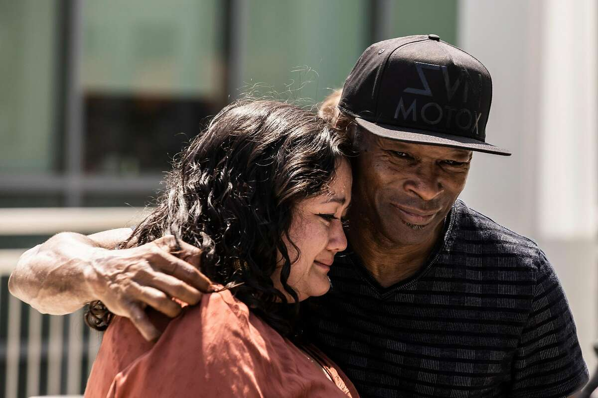 Angie Brey (left), partner of the late Gregory Turnage Jr., embraces Gregory Turnage Sr. outside the courthouse.